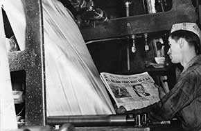 Cleveland Press employee watches newspapers roll off presses, 1938